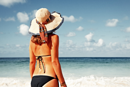 sunburnt: Woman in bikini and hat on tropical beach Stock Photo