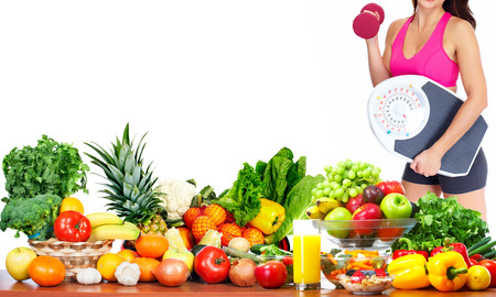 vegetables white background: Woman with scales and dumbbell fruits and vegetables background Stock Photo