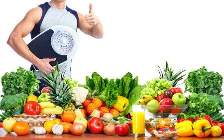 weigher: Man with scales fruits and vegetables background Stock Photo