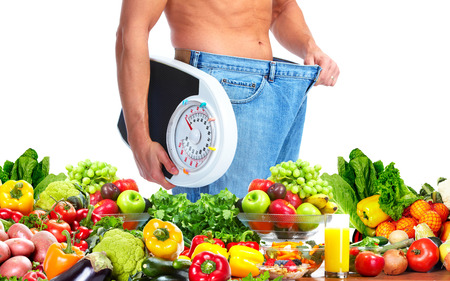 fat belly: Man with scales fruits and vegetables background Stock Photo