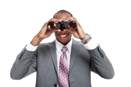 African-American businessman with binoculars  isolated white background. photo