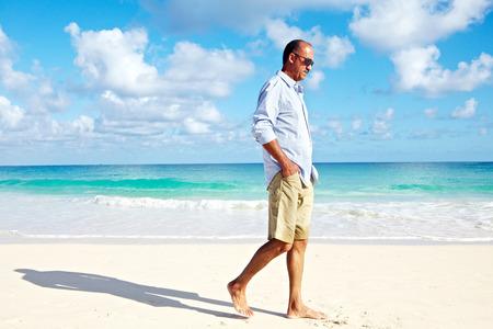 beach clothes: Man walking on sandy beach. Stock Photo