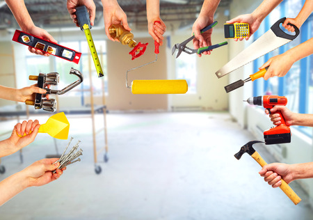 home renovation: Hands with construction tools.