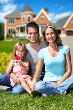 real estate investment: Happy family near new house.