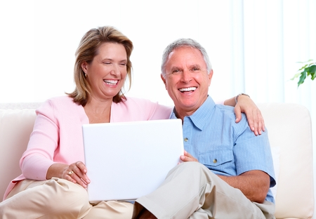 home finances: Senior couple at home with computer.