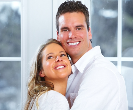 young couple smiling: Young couple at home.