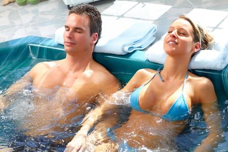 hot tub: Young couple relaxing in bath tub.