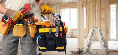 electrician tools: Builder handyman with construction tools.