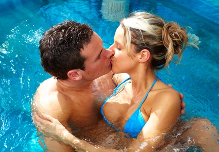 love hot body: Young couple kissing in pool Stock Photo