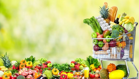 groceries shopping: Shopping cart with vegetables and fruits. Stock Photo