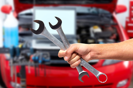 hand brake: Hand of car mechanic with wrench.
