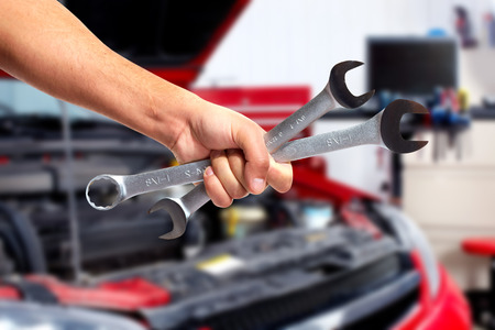 Hand of car mechanic with wrench. photo