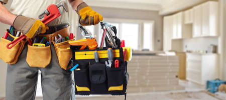 plumbing tools: Builder handyman with construction tools.