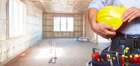 tools: Builder handyman with construction tools. House renovation background.