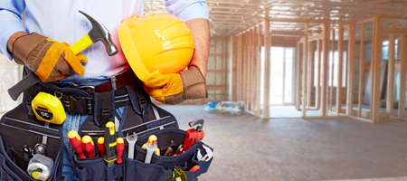 home builder: Builder handyman with construction tools. House renovation background.