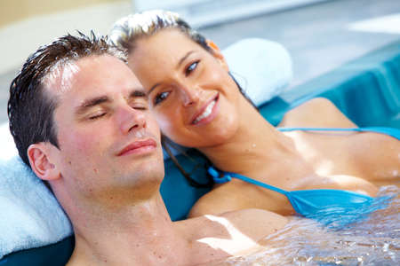 hot tub: Young couple relaxing in hot tub. Summer vacation.