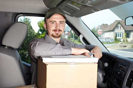 parcel service: Young delivery man in the car. Parcel service. Stock Photo