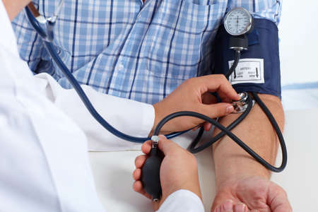 Doctor checking old man patient arterial blood pressure. Health care. Stock Photo