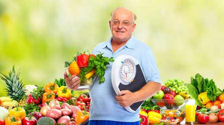 ancianos felices: Hombre mayor con escalas y verduras sobre fondo verde.