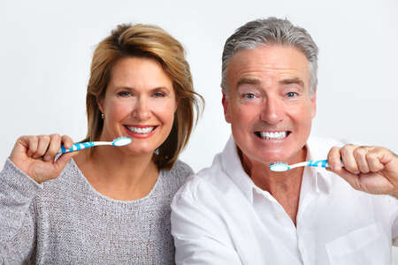 tooth whitening: Happy elderly couple with toothbrush. Dental health.