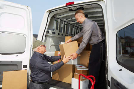 ship parcel: Delivery men with parcels near cargo truck. Post service. Stock Photo
