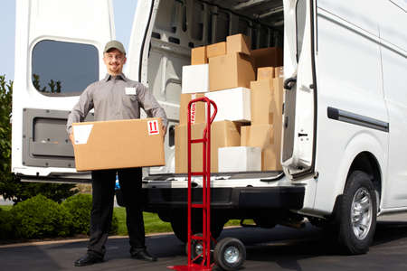 goods: Young delivery man with parcel near cargo truck. Shipping service.