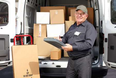 delivery service: Senior delivery man with parcel near truck. Shipping service.
