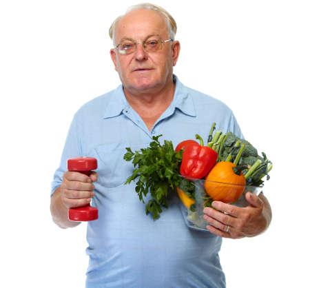 Homem idoso com legumes e halteres isoladas sobre o fundo branco.