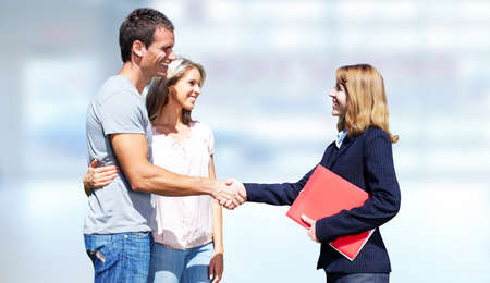 property agent: Young couple with agent realtor over blue background. Stock Photo