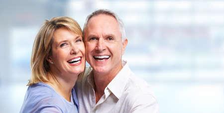 retirement: Happy senior couple portrait over blue background.