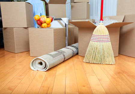 escoba: Moviendo cajas en el nuevo apartamento. Concepto de bienes raíces. Foto de archivo