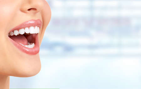 tooth whitening: Laughing woman mouth with great teeth over blue background. Stock Photo