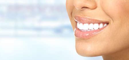dientes: Riendo mujer boca con grandes dientes sobre fondo azul.