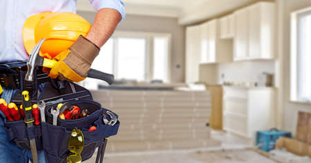 renovation house: Builder handyman with construction tools. House renovation background.