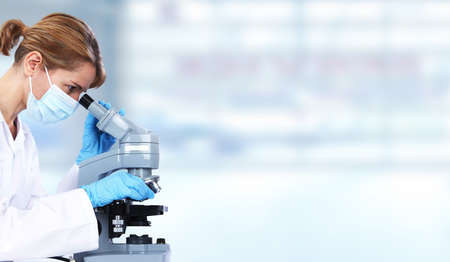 researching: Doctor woman with microscope in laboratory. Scientific research. Stock Photo
