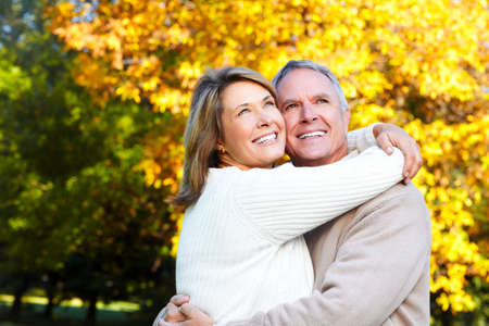 couple nature: Happy senior couple in park. Autumn and fall background.