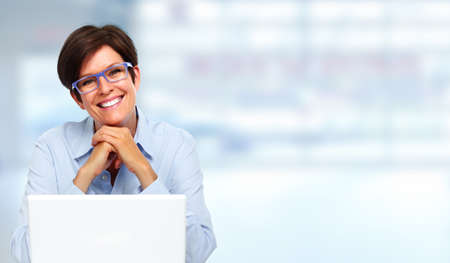 working on laptop: Beautiful business lady with laptop computer in office. Stock Photo