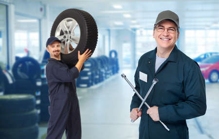 car service station: Smiling repairman with tire wrench in car repair service. Stock Photo