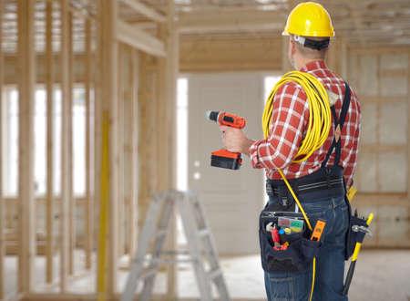 Elektriker Mann mit Bohrmaschine und Draht-Leitung über Bau-Hintergrund. Standard-Bild