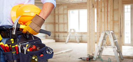 plumbing tools: Builder handyman with construction tools. House renovation background.