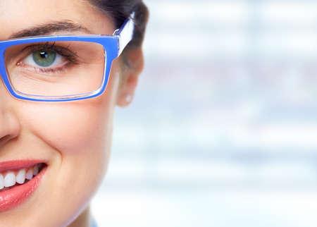 vidrio: Ojo de la mujer hermosa con los vidrios sobre el fondo azul de la bandera.