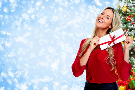 christmas bonus: Happy  woman with envelope over Christmas background.