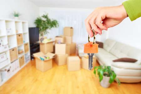 llaves: Mano con llave de la casa. Inmobiliario y fondo en movimiento. Foto de archivo