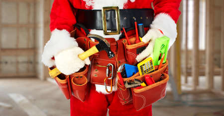 christmas costume: Santa Worker with a tool belt construction background.