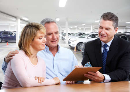car loans: Senior smiling couple with car dealer. Auto rental background.