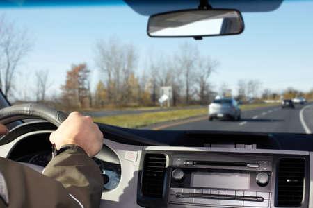 camion: Mano del hombre que conducía en una carretera. Concepto de seguro del conductor.