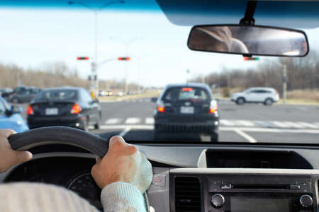 road traffic: Hand of man driving on a highway. Driver insurance concept.