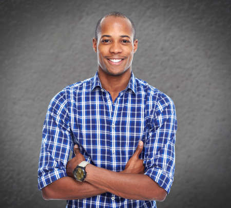 africanamerican: Young smiling African-american businessman over grey wall background.