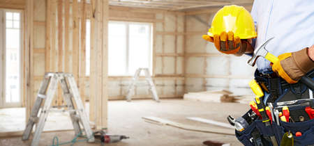 residential: Builder handyman with construction tools. House renovation background.