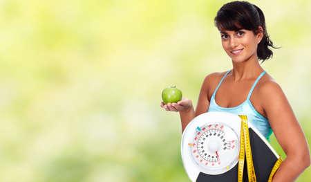 Junge Frau mit Apfel und Waagen. Gesunde Ernährung und Gewichtsverlust.